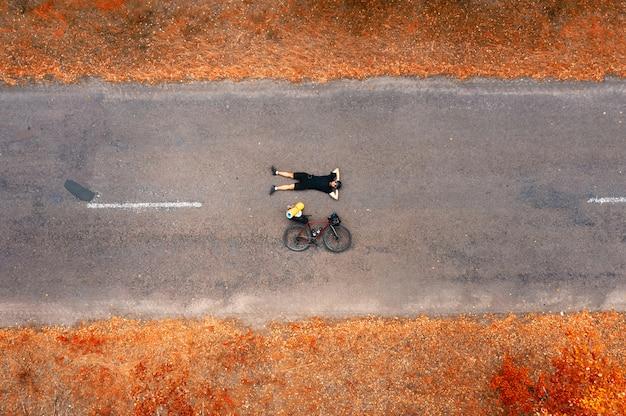 Вид сверху велосипедиста с дорожным велосипедом, лежащим на асфальте. Premium Фотографии