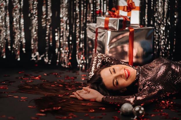 ハートとギフトの形で紙吹雪で床に光沢のある服を着て横たわっている女の子の平面図。 Premium写真
