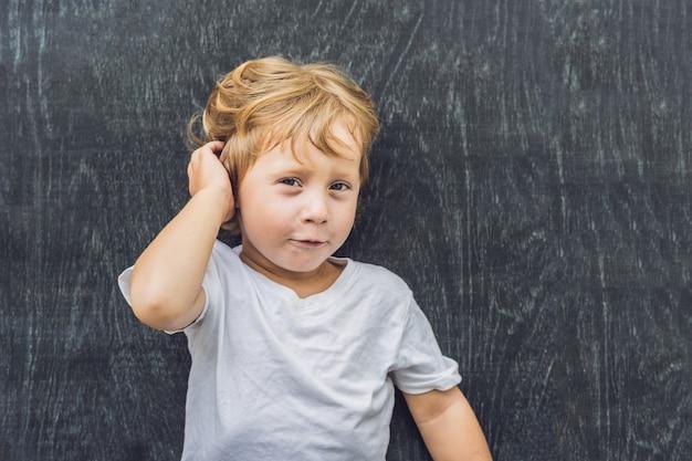 Вид сверху маленького белокурого мальчика с пространством для текста и символов на старом деревянном. Premium Фотографии