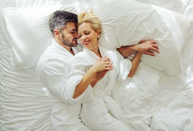 Вид сверху влюбленной пары среднего возраста в халатах на медовый месяц, лежа в постели и обнимаясь. Premium Фотографии