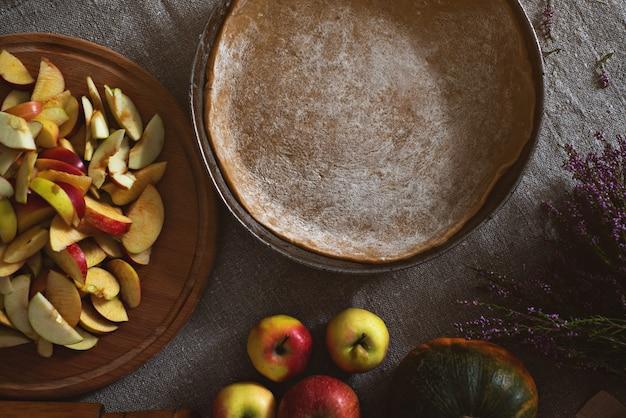 Вид сверху на сковороду с тестом для пирогов, доску с горкой яблок и тыкв Premium Фотографии