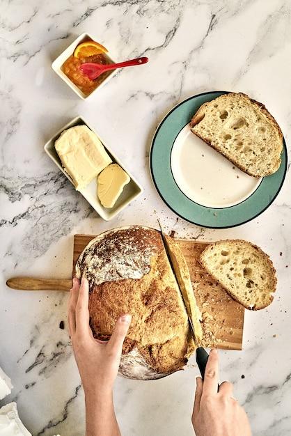 Вид сверху человека, нарезавшего свежеиспеченный хлеб на деревянной доске с маслом и мармеладом Бесплатные Фотографии