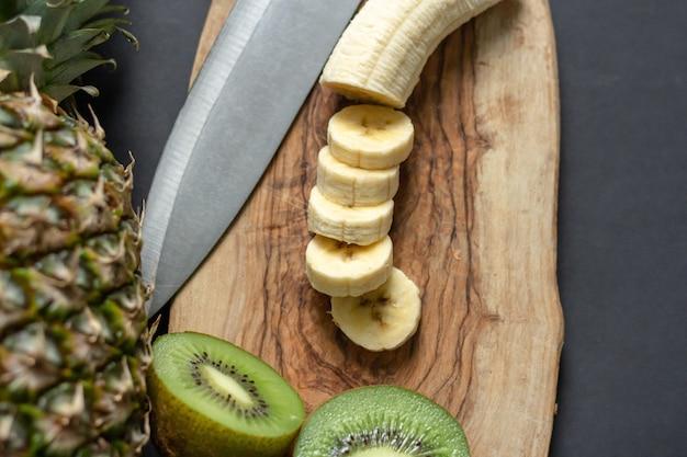 Вид сверху ананаса на столе с нарезанными бананами и киви на деревянной разделочной доске Бесплатные Фотографии