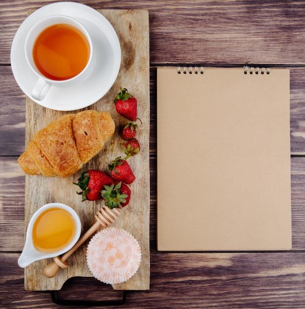 Взгляд сверху sketchbook и и свежего зрелого меда круассана клубники и чашки чая на деревянной разделочной доске на деревенском Бесплатные Фотографии