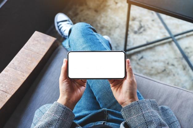 Вид сверху женщины, держащей черный мобильный телефон с пустым белым экраном рабочего стола Premium Фотографии