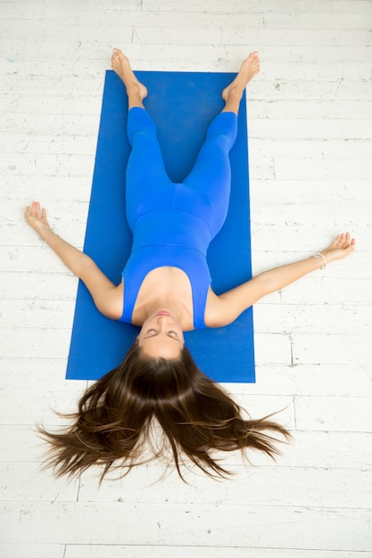 top view of a woman in corpse pose white studio photo free download