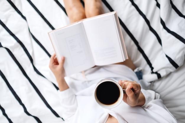 Вид сверху женщина читает книгу и пьет горячий кофе в белой уютной постели у себя дома по утрам Premium Фотографии