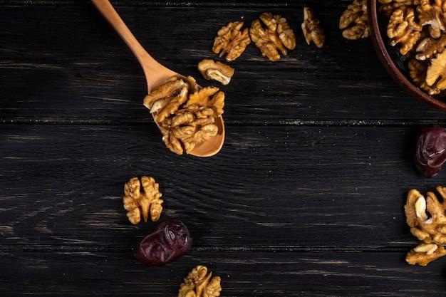 Вид сверху деревянной ложкой с грецкими орехами и сладкие сушеные фрукты на деревянном Бесплатные Фотографии
