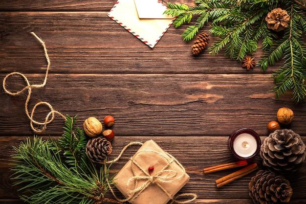 クリスマスのための松の木の枝とキャンドルで飾られた木製のテーブルの上面図 無料写真