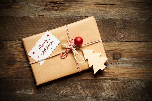 木の表面に、メリークリスマスと書かれたカードが付いた包まれたクリスマスプレゼントの上面図 無料写真