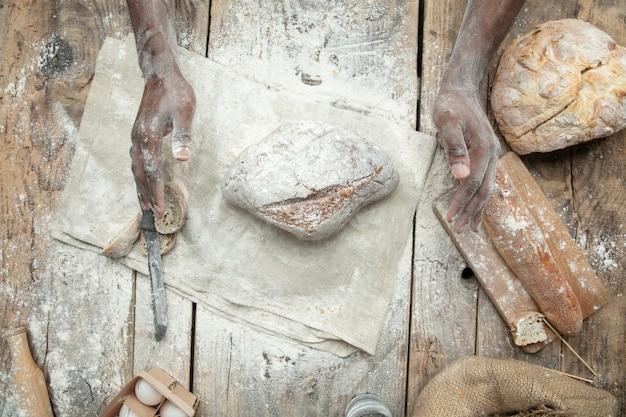Вид сверху афроамериканца готовит свежие хлопья, хлеб, отруби на деревянном столе Бесплатные Фотографии