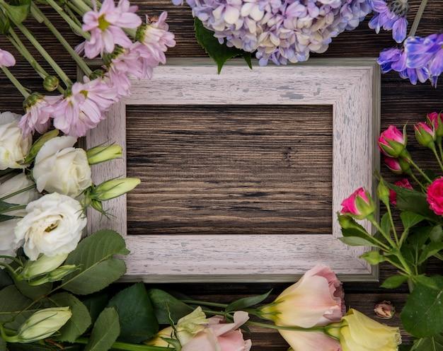 コピースペースと木製の背景に葉を持つライラックバラデイジーなどの素晴らしい花の上面図 無料写真
