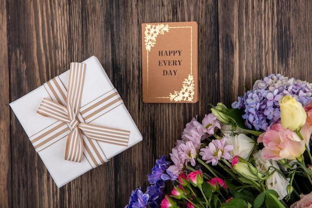木製の背景に白いギフトボックスとライラックバラデイジーなどの素晴らしい花の上面図 無料写真