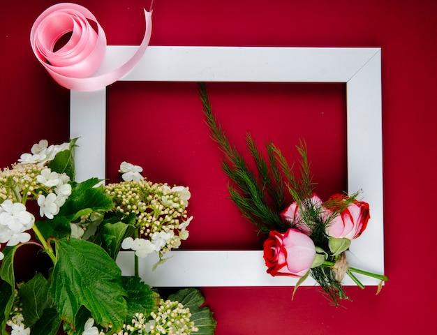 赤い背景のフェンネルと咲くガマズミ属の木と赤いバラと空の図枠の平面図 無料写真