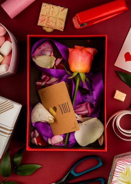 はさみ、ホッチキス、ホワイトチョコレート、マシュマロと赤いテーブルにサンゴ色のバラの花と紫のリボンと花びらの小さな紙カードのオープンギフトボックスの平面図 無料写真
