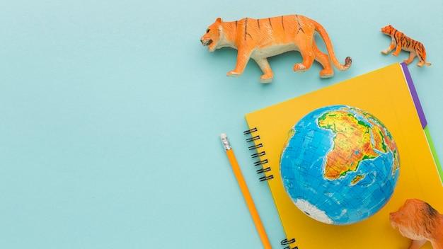 Вид сверху фигурок животных с блокнотом и планеты земля на день животных Бесплатные Фотографии