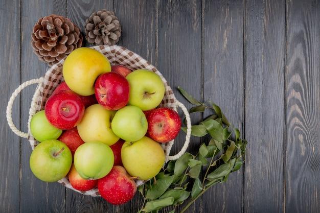 Вид сверху яблок в корзине с шишкой и листьев на деревянных фоне с копией пространства Бесплатные Фотографии