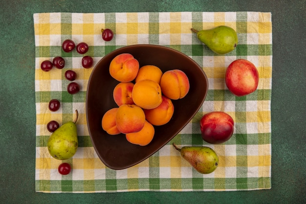 ボウルにアプリコットの上面図と緑の背景の格子縞の布に梨桃桜のパターン 無料写真