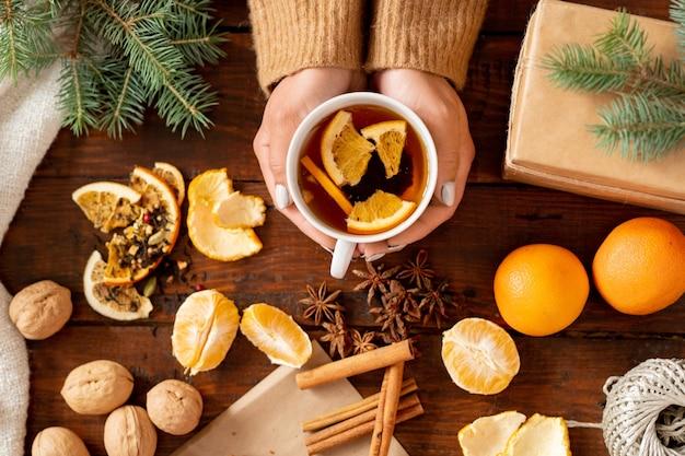 木製のテーブルに新鮮なフルーツ、スパイス、クルミに囲まれた女性によって開催されたオレンジスライスと香り豊かなお茶のトップビュー Premium写真