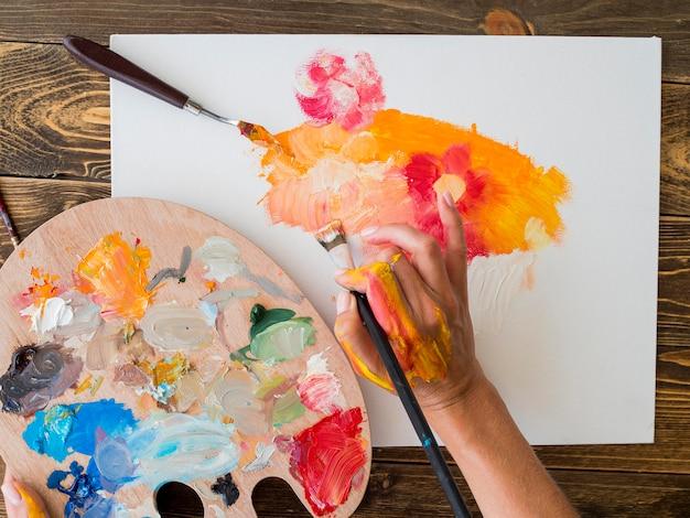 ブラシとパレットでペイントするアーティストの平面図 無料写真