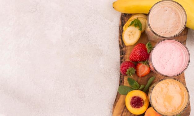 Вид сверху ассортимента молочных коктейлей с фруктами и копией пространства Premium Фотографии