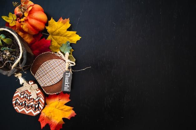黒い木の表面にカボチャと秋のカエデの葉の上面図 無料写真