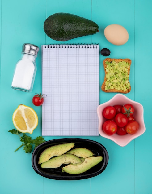 Вид сверху авокадо с яйцом, ломтиком жареного хлеба с оливковым маслом и мякотью авокадо с лимоном Бесплатные Фотографии