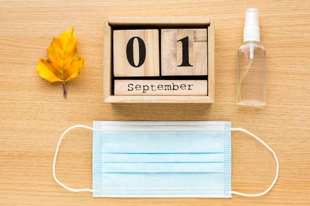Вид сверху обратно в школу предметов первой необходимости с медицинской маской и календарем Бесплатные Фотографии