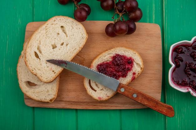 まな板にナイフでラズベリージャムを塗ったバゲットスライスと緑の背景にラズベリージャムのボウルとブドウの上面図 無料写真