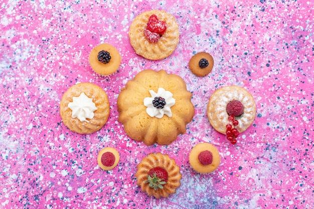 Вид сверху запеченных вкусных тортов со сливками вместе с разными ягодами на ярко-фиолетовом столе, бисквитный ягодный сладкий чай для выпечки Бесплатные Фотографии