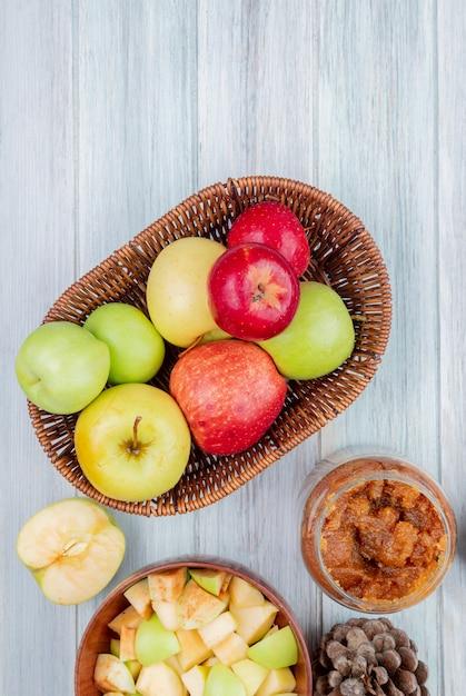 Вид сверху корзина яблок с банкой яблочного варенья чаша из яблок кубиками половинки яблока и шишка на деревянный стол Бесплатные Фотографии
