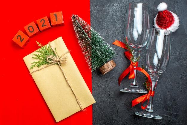 빨간색과 검은 색 배경에 아름다운 선물 크리스마스 트리 번호 산타 클로스 모자의 상위 뷰 무료 사진