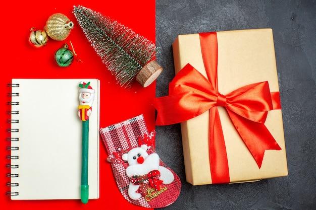 Вид сверху красивой подарочной рождественской елки носка с ручкой на красном и черном фоне Бесплатные Фотографии