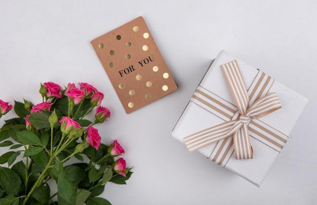 흰색 배경에 잎과 흰색 선물 상자와 함께 아름 다운 핑크 장미의 상위 뷰 무료 사진
