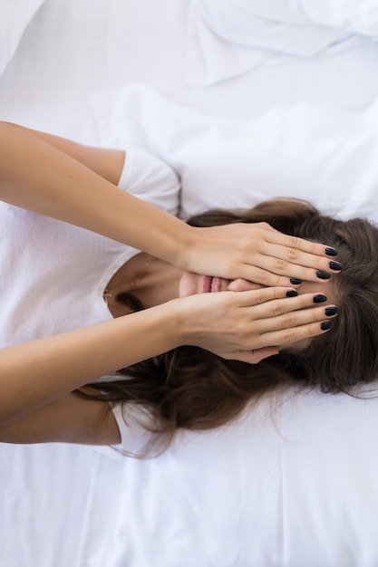 ベッドに横たわっている間彼女の顔を覆っている美しいセクシーな若い女性のトップビュー 無料写真
