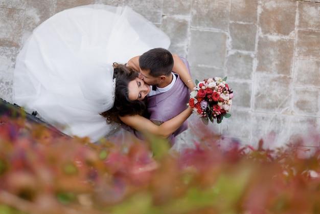 屋外キス、結婚の概念であるウェディングブーケを持つ美しい結婚式のカップルの平面図 無料写真