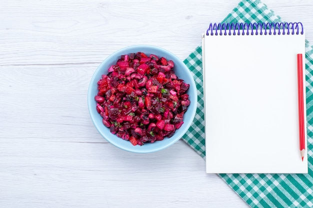 ライトデスクにメモ帳付きの青いプレートの内側に緑でスライスされたビートサラダの上面図、サラダ野菜食品食事の健康 無料写真