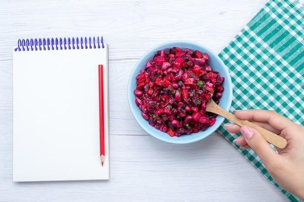 白い机の上のメモ帳と青いプレートの内側に緑でスライスされたビートサラダの上面図、サラダ野菜ビタミン食品食事の健康 無料写真