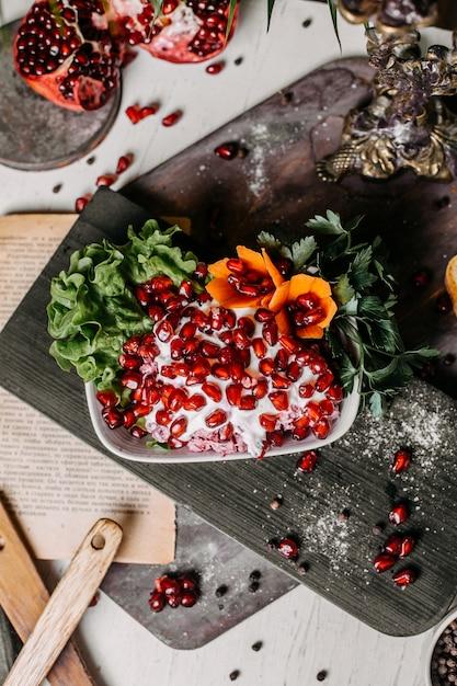 木の板にソースマヨネーズとザクロのビートサラダのトップビュー 無料写真