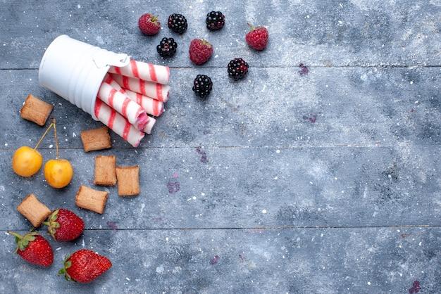 明るい机の上にピンクのスティックキャンディー、フルーツベリークッキーとベリーとクッキーの上面図 無料写真