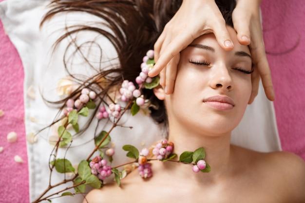 花で横になっているスパで美しい女性のトップビュー 無料写真