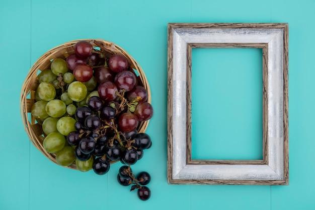 コピースペースと青い背景のフレームとバスケットの黒と白のブドウの上面図 無料写真