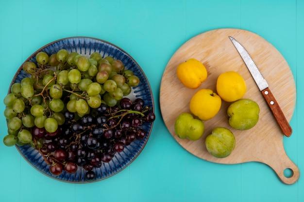 プレートと緑のプルオットアプリコットの黒と白のブドウの上面図青い背景のまな板にナイフで 無料写真