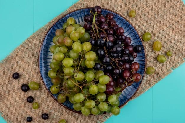 青の背景の荒布のプレートの黒と白のブドウの上面図 無料写真