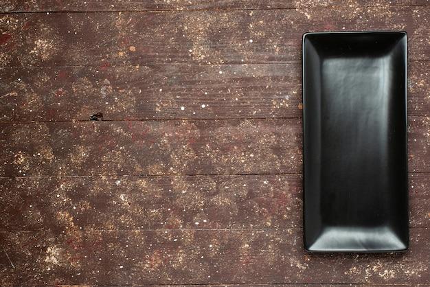茶色の素朴な、ケーキ食品焼き甘い机、木で長い形の黒いケーキ型の上面図 無料写真