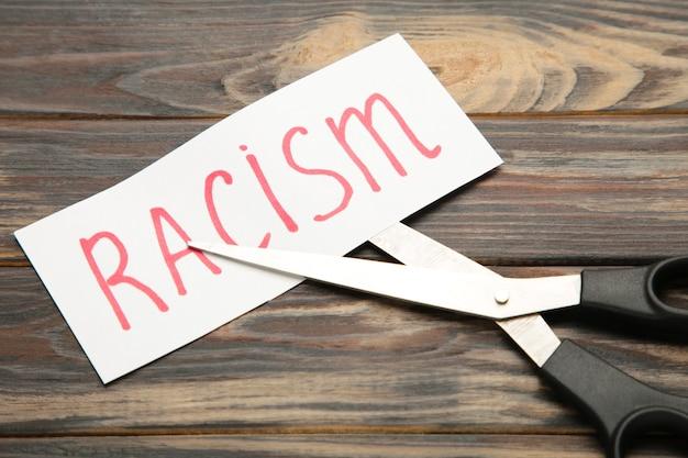 Вид сверху на черные ножницы и вырезанную бумажную карточку со словом «расизм» Premium Фотографии