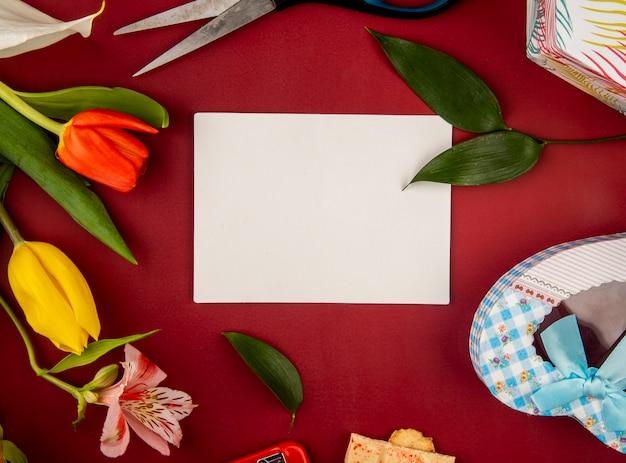 赤いテーブルに白紙のグリーティングカードとハート型のギフトボックスとアルストロメリアの花とチューリップの平面図 無料写真