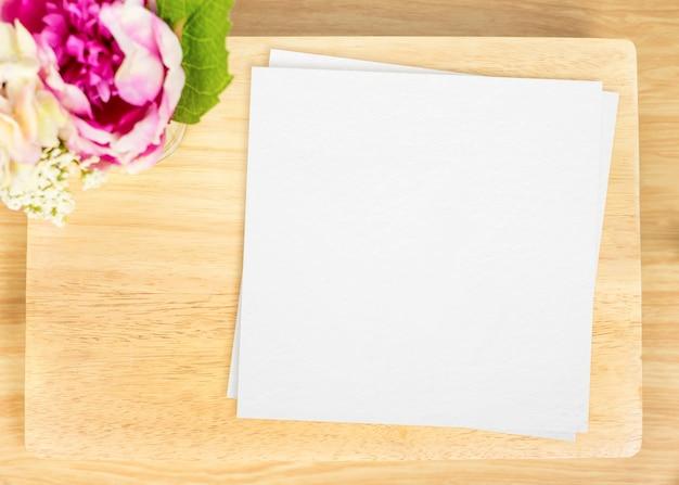 テーブルの上に白い紙と花の鍋と空の木製のプレートのトップビュー Premium写真