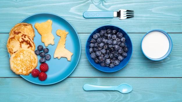 Вид сверху черники с детским питанием и столовыми приборами Бесплатные Фотографии