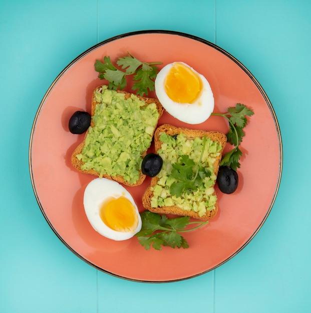 青にオリーブオンオレンジプレートとアボカドパルプとトーストしたパンとゆで卵の平面図 無料写真